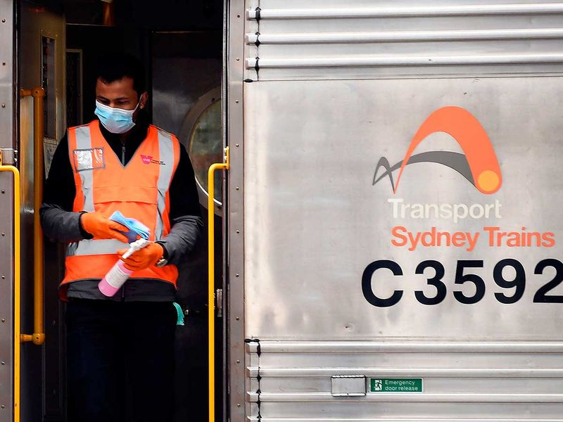 An employee disinfects a train in the central business district of Sydney