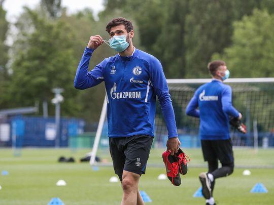 Schalke's German midfielder Daniel Caligiuri wears a face mask as he leaves after a training session.