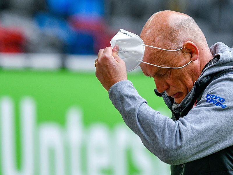 Fortuna Dusseldorf coach Uwe Roesler removes a protective face mask, as play resumes behind closed doors following the outbreak of coronavirus