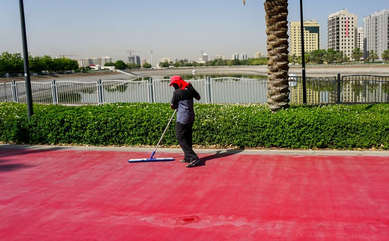 A cleaner sweeps the empty running track at Al Nahda Pond Park