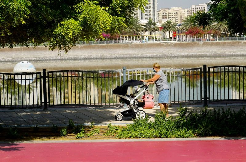 A grandmother pushes her grandchild in Al Nahda Pond Park