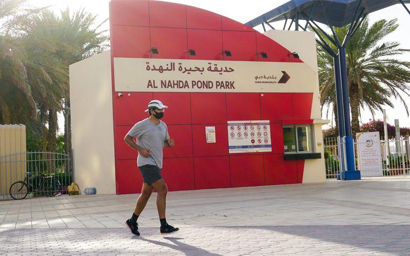 A jogger runs past Al Nahda Pond Park before opening