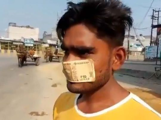 Man wears bank note as a mask