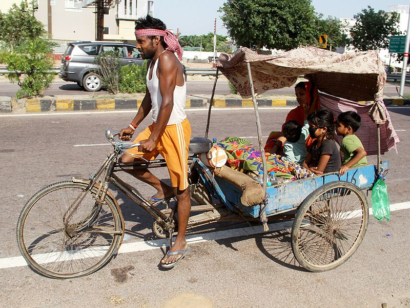 A man rides a tricycle along with his family to go to their native place in Lucknow.