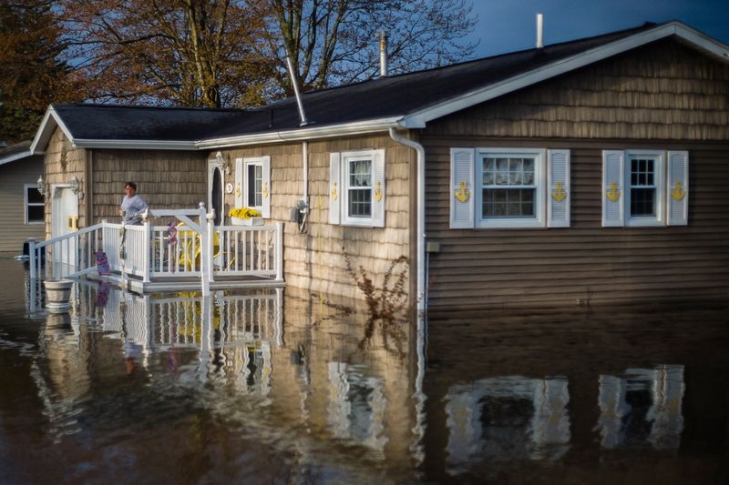 Carol Ouellette stands on her front porch, surrounded by floodwater, in Beaverton.