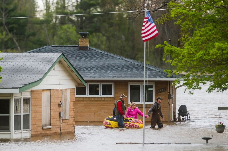 People help each other travel from one home to another using an inflatable raft on Oakridge Road on Wixom Lake, in Beaverton.