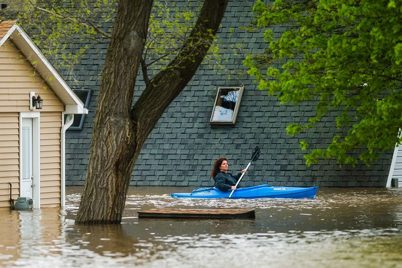 People use kayaks to assess the damage at homes in their neighborhood on Oakridge Road on Wixom Lake.