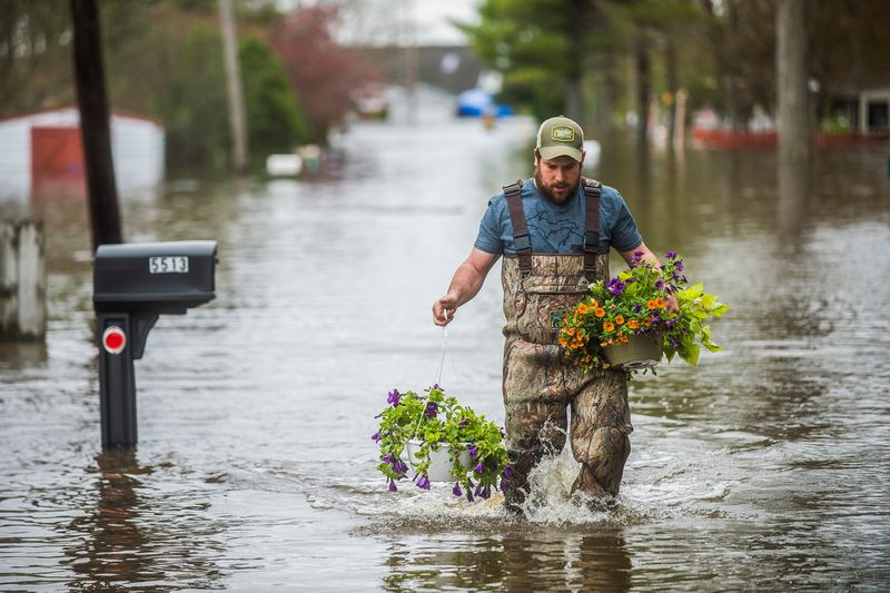 Tyler Marciniak, of Grand Rapids, carries hanging plants through floodwaters as he helps his father, assess the damage to his home on Red Oak Drive on Wixom Lake.