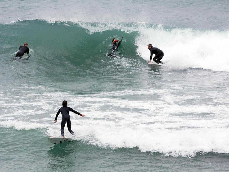 Surfers take to the water at Cottesloe beach in Perth