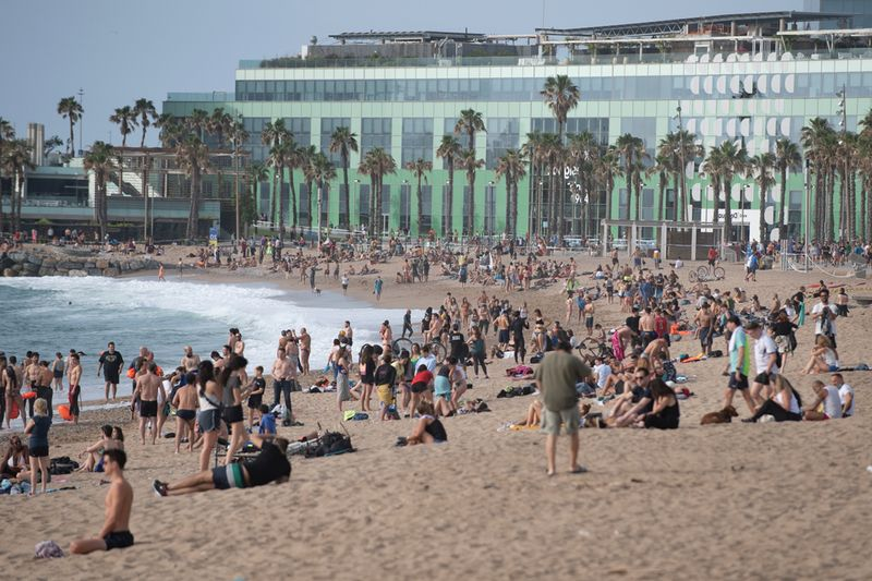 People enjoy a morning out at La Barceloneta Beach in Barcelona.