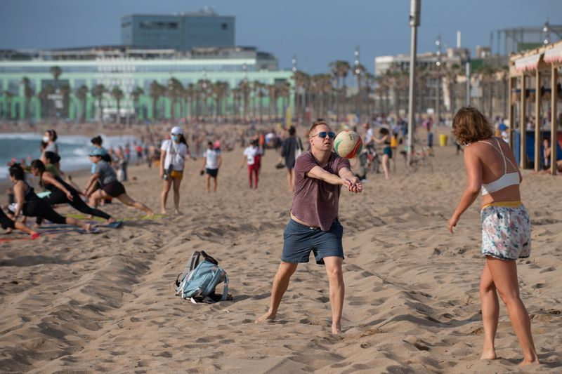 People play beach volley at La Barceloneta Beach in Barcelona.