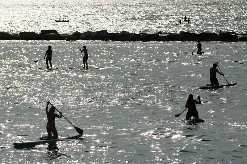 People practise paddleboarding at dawn at La Barceloneta Beach in Barcelona.