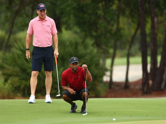 Tiger Woods lines up a putt as Phil Mickelson looks on