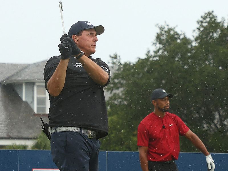 Tiger Woods watches a shot by Phil Mickelson