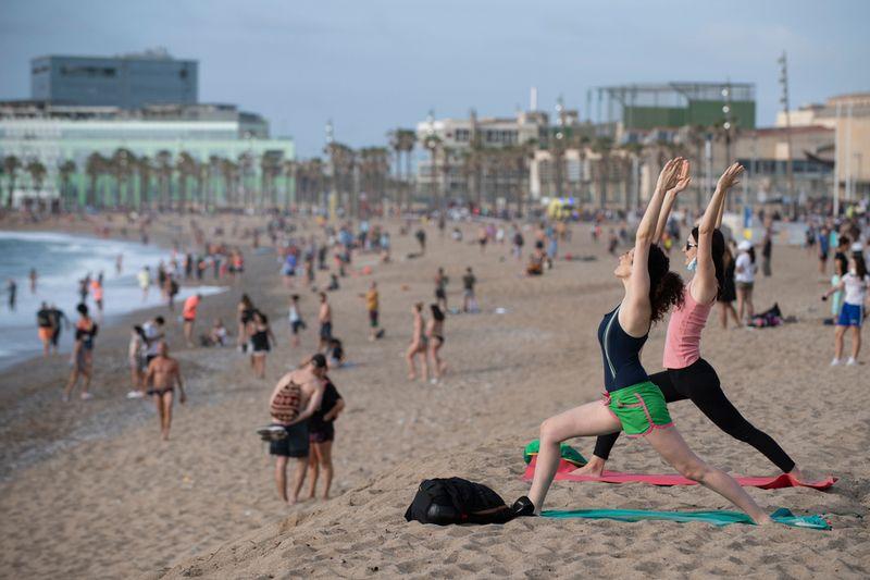 Two women wearing practise yoga at dawn at La Barceloneta Beach in Barcelona.