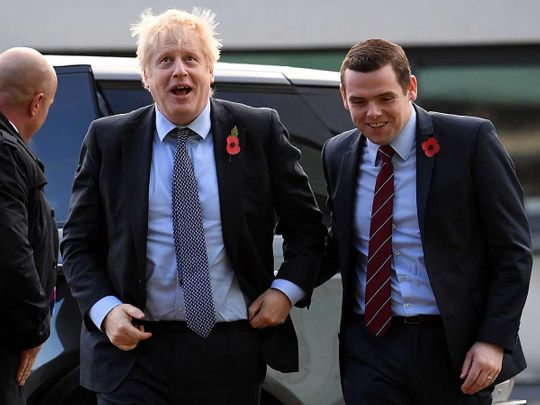 Britain's Prime Minister Boris Johnson (C) is greeted by Conservative party candidate for Moray, Douglas Ross