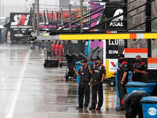 Crew members watch as rain falls before a NASCAR Cup Series auto race at Charlotte Motor Speedway