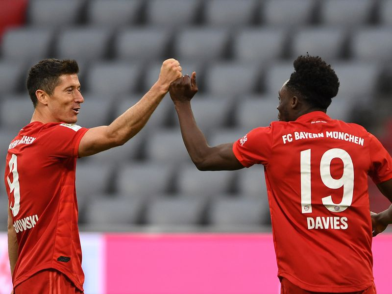 Bayern Munich's Robert Lewandowski, left, and teammate Alphonso Davies celebrate the fifth goal against Fortuna Duesseldorf