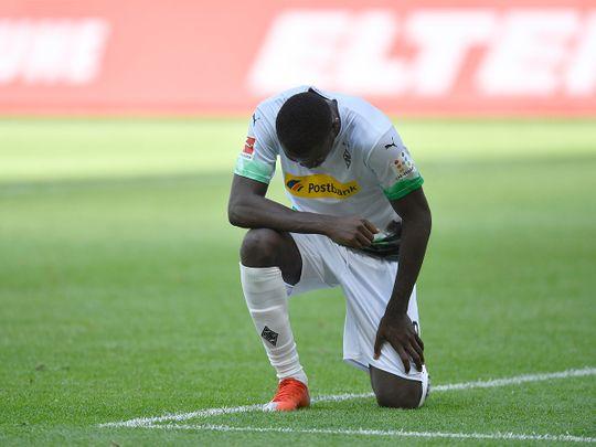 Borussia Moenchengladbach's Marcus Thuram takes a knee for George Floyd.