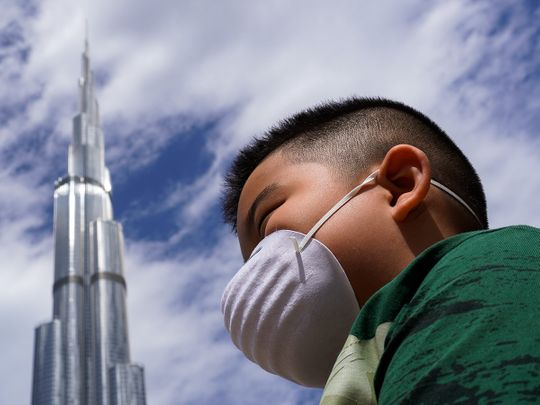 boy wearing mask, burj khalifa, covid-19 in uae