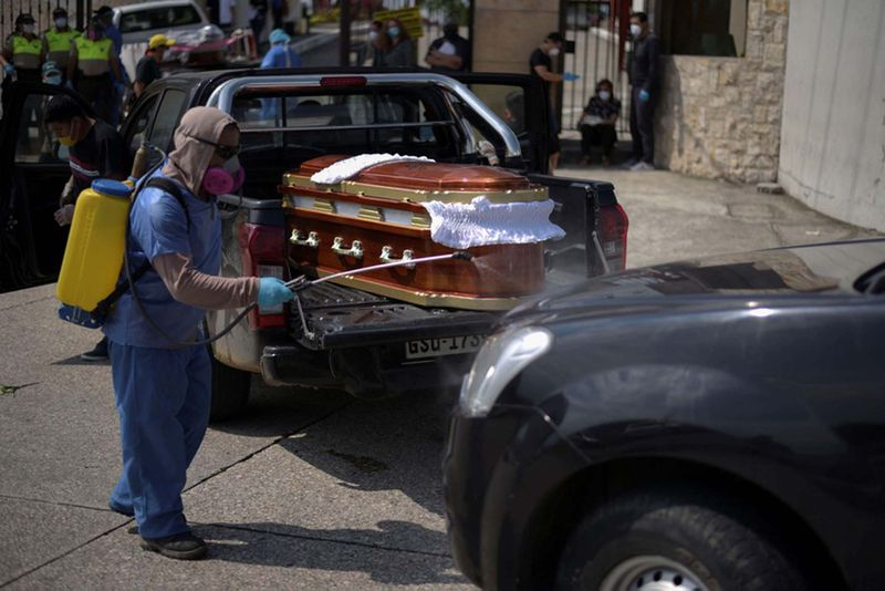 A worker sprays disinfectant on a vehicle carrying a coffin lined up to enter a cemetery as Ecuador's government announced on Thursday it was building a