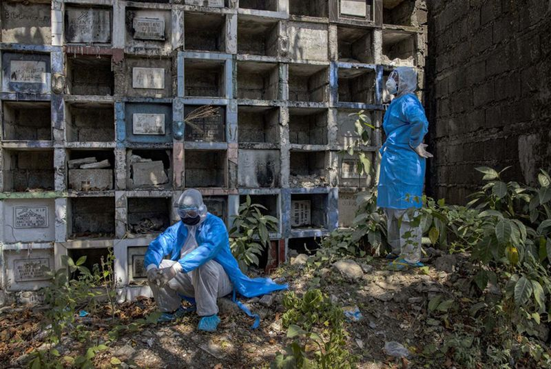 Funeral workers wearing protective suits take a break before transporting the body of a person presumed to have died of the coronavirus at a public cemetery on April 3, 2020 in Quezon city, Metro Manila, Philippines.