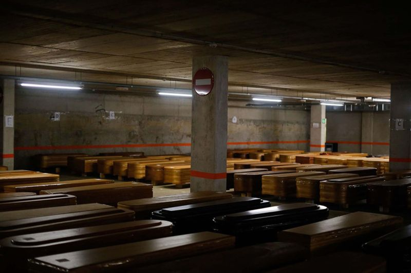 General view taken on April 3, 2020 of coffins, containing the bodies of COVID-19 victims, at the parking of the Collserola funeral parlour in Montcada i Reixac, near Barcelona.