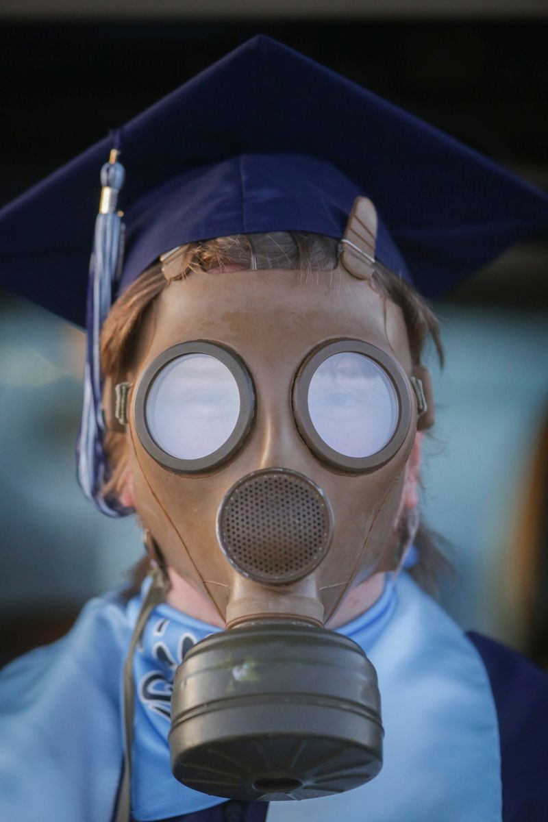 Isaac Hill wears a gas mask along with his cap and gown during the graduation ceremony for Skyline High School at Motor Vu Drive-In in Idaho Falls, Idaho on Wednesday, May 27, 2020.