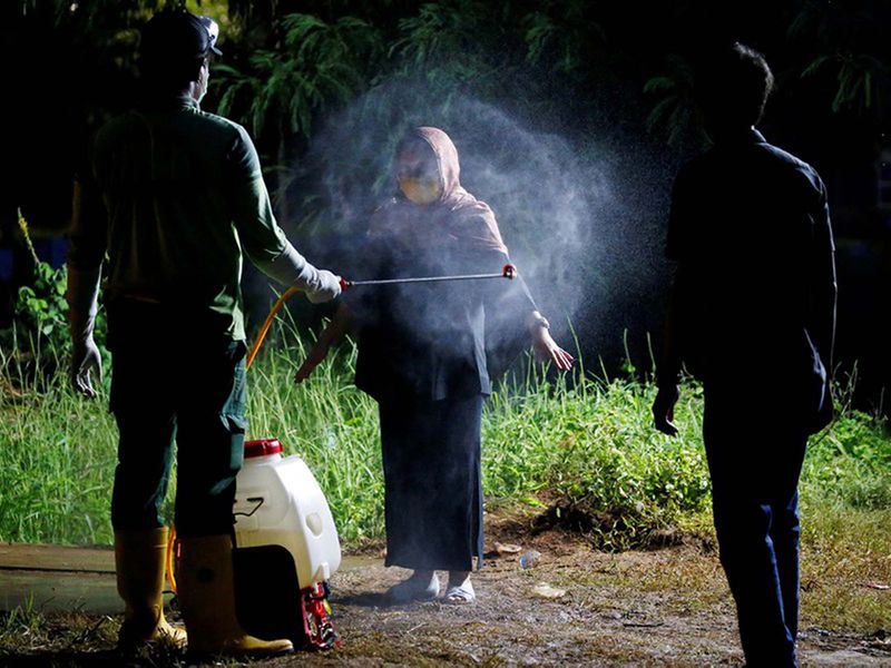Municipality worker sprays disinfectant on a relative of a COVID-19 victim during a funeral in Jakarta, Indonesia, March 31, 2020.