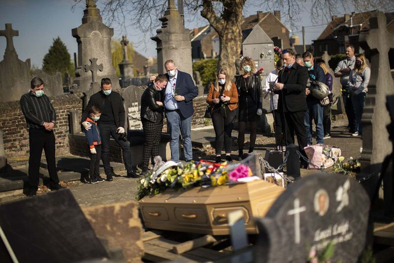 Relatives of Margodt Genevieve, who died due to Covid-19, grieve during her funeral ceremony at the Montignies cemetery in Charleroi, Belgium, Wednesday, April 8, 2020.