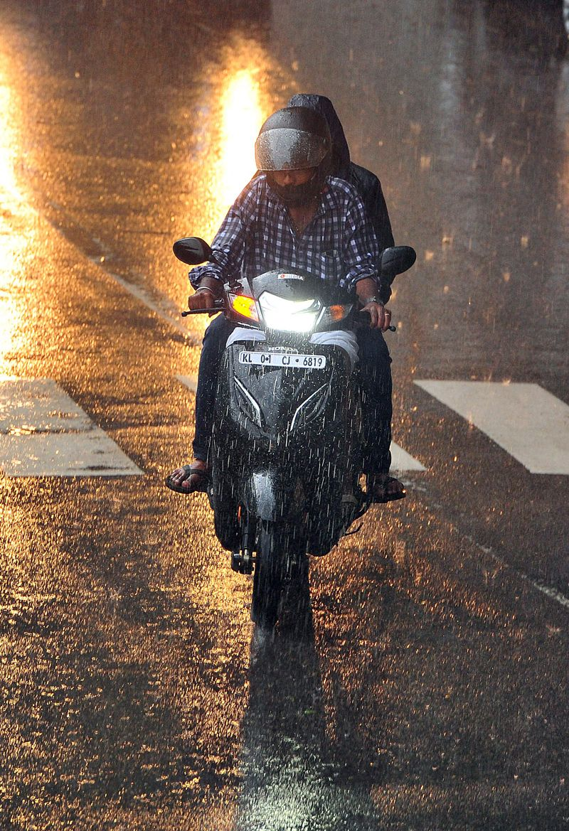 A man rides a scooty during rainfall, in Thiruvananthapuram.