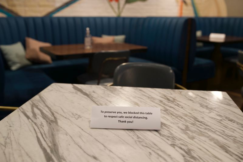 London Dairy Cafe in DIFC placing table signs to prevent customers from getting too close
