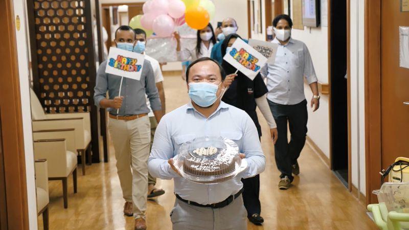 NAT 200602 ASIF GANI Colleagues walking with cake-1591083768713
