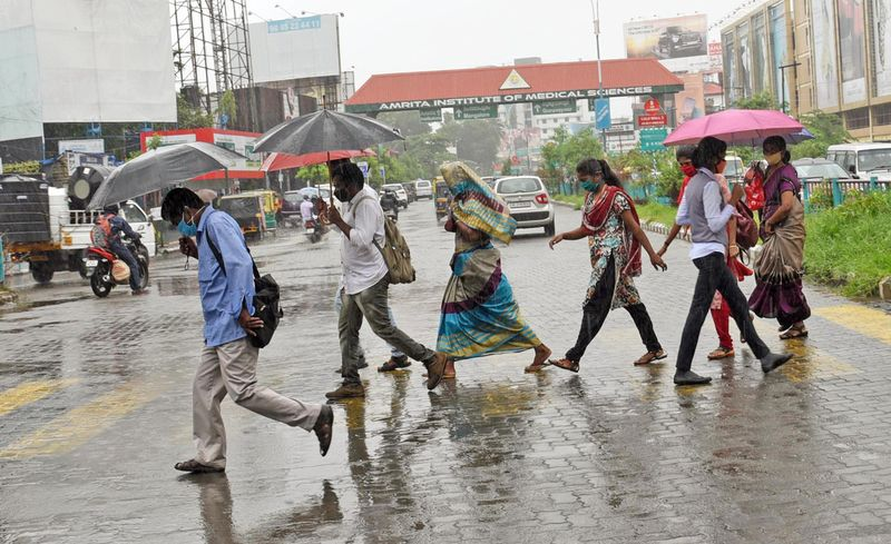 People crossing a road during heavy rain, in Kochi on Tuesday.