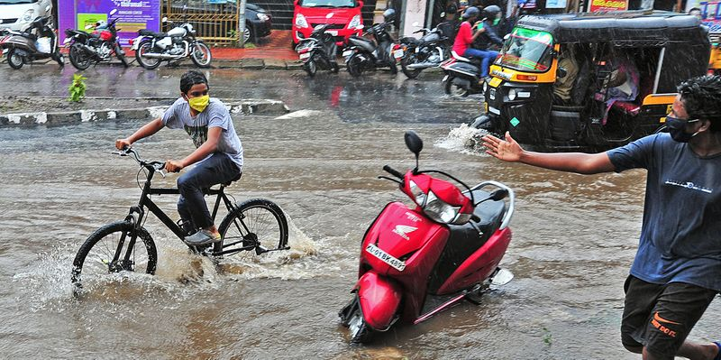 Vehicles wade through a waterlogged street during heavy rain, in Thiruvananthapuram.
