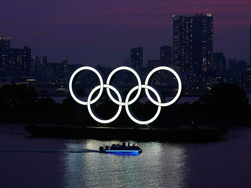The Olympic rings float in the water at sunset in Odaiba. The Tokyo Olympics were postponed in March and are now scheduled to open on July 23, 2021.