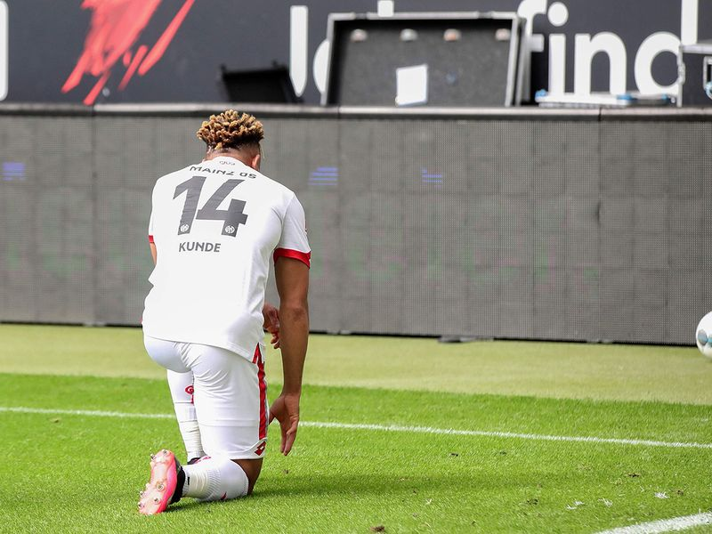 Mainz' Cameroonian midfielder Kunde Malong take a knee in solidarity with protests raging across the United States over the death of George Floyd, an unarmed black man who died during an arrest, after scoring during the German first division Bundesliga football match Eintracht Frankfurt v 1. FSV Mainz