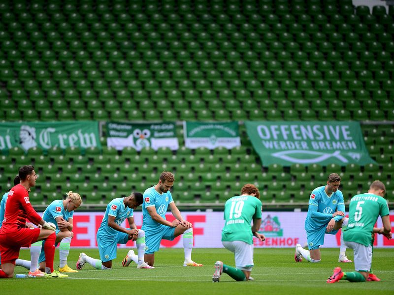 Players from both teams take a knee in solidarity with protests raging across the US over the death of George Floyd, prior to the German first division Bundesliga football match SV Werder Bremen v VfL Wolfsbur