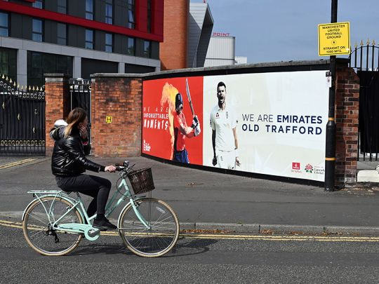 A woman cycles past Old Trafford cricket ground in Manchester where West Indies will play England in a Test series