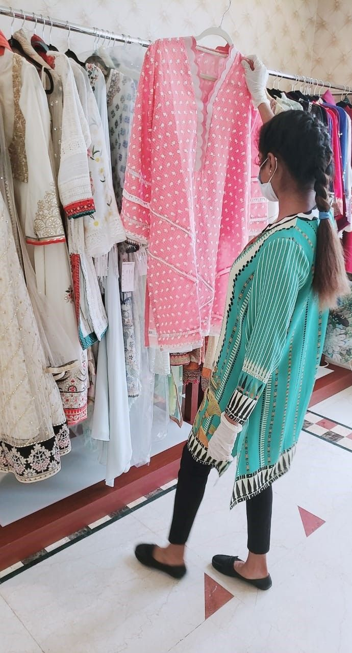 A customer checking out a cotton suit at Ensemble
