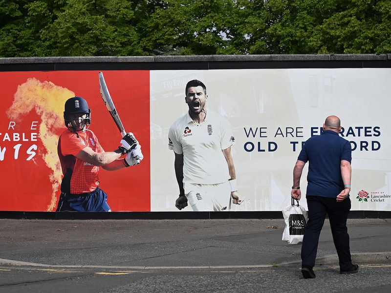 A pedestrian walks past a poster advertising the England cricket matches against the West Indies at Old Trafford in Manchester.