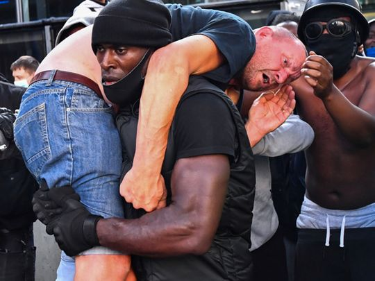 A black protester carried a 'far-right' protester to safety after he was beaten up in clashes in London, photo goes viral