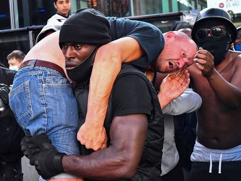 A protester carries an injured counter-protester to safety, near the Waterloo station during a Black Lives Matter protest following the death of George Floyd in Minneapolis police custody, in London, Britain, June 13, 2020. 1