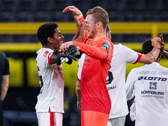 Mainz's Ridle Baku, left, and Florian Mueller celebrate after defeating Dortmund