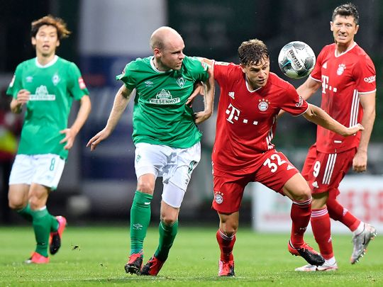 Bayern's Joshua Kimmich, second right, fights for the ball with Bremen's Davy Klaassen during the German Bundesliga soccer match between Werder Bremen and Bayern Munich in Bremen, Germany, Tuesday, June 16, 2020. Because of the coronavirus outbreak all soccer matches of the German Bundesliga take place without spectators. (AP Photo/Martin Meissner, Pool)