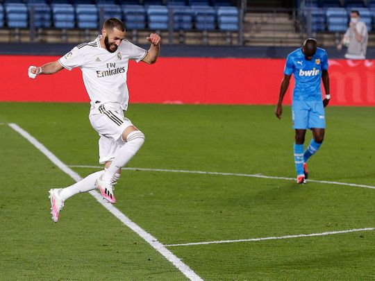 Real Madrid's Karim Benzema celebrates after scoring his side's third goal during the Spanish La Liga soccer match between Real Madrid and Valencia at Alfredo di Stefano stadium in Madrid, Spain, Thursday, June 18, 2020. (AP Photo/Manu Fernandez)