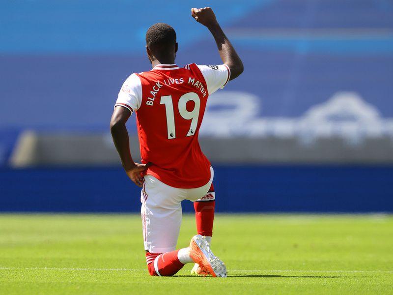 Arsenal's Nicolas Pepe kneels before the game against Brighton.