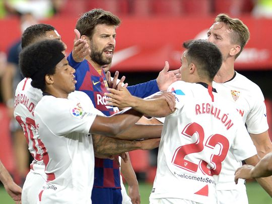 Barcelona's Spanish defender Gerard Pique (C) argues with Sevilla's Spanish defender Sergio Reguilon (R) during the Spanish league football match between Sevilla FC and FC Barcelona at the Ramon Sanchez Pizjuan stadium in Seville on June 19, 2020. (Photo by CRISTINA QUICLER / AFP)
