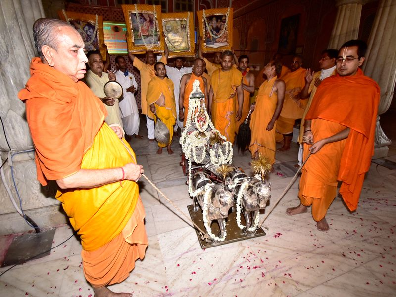 Priests pull the silver chariot of Govind Dev ji during Rath Yatra or chariot procession inside temple premises at Thikana Mandir Shri Govinddevji Maharaj in Jaipur on Tuesday.