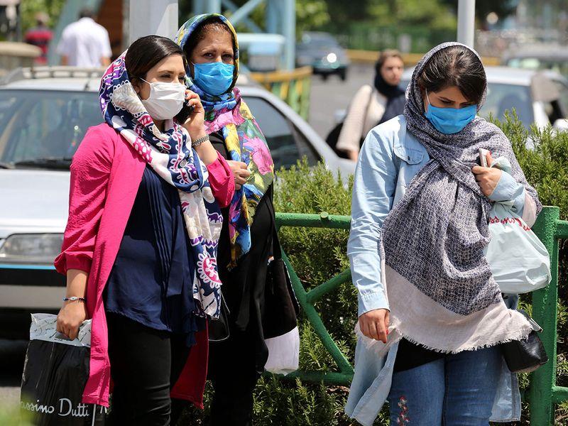 Pedestrians, wearing protective masks, walk along a street in  Tehran on June 28, 2020.